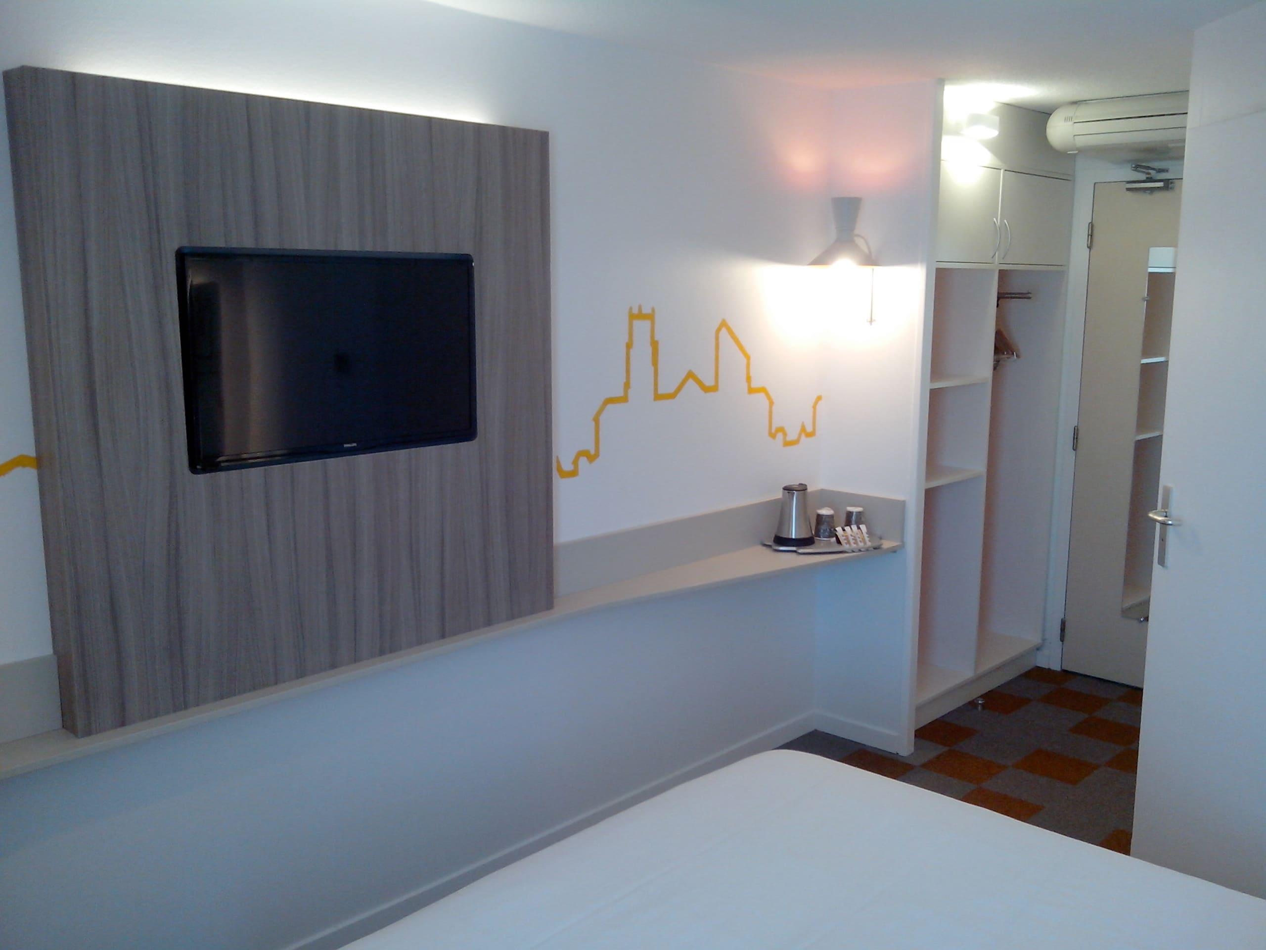 Chambre de l'Hôtel Comfort à Albi avec décorations jaunes sur les murs