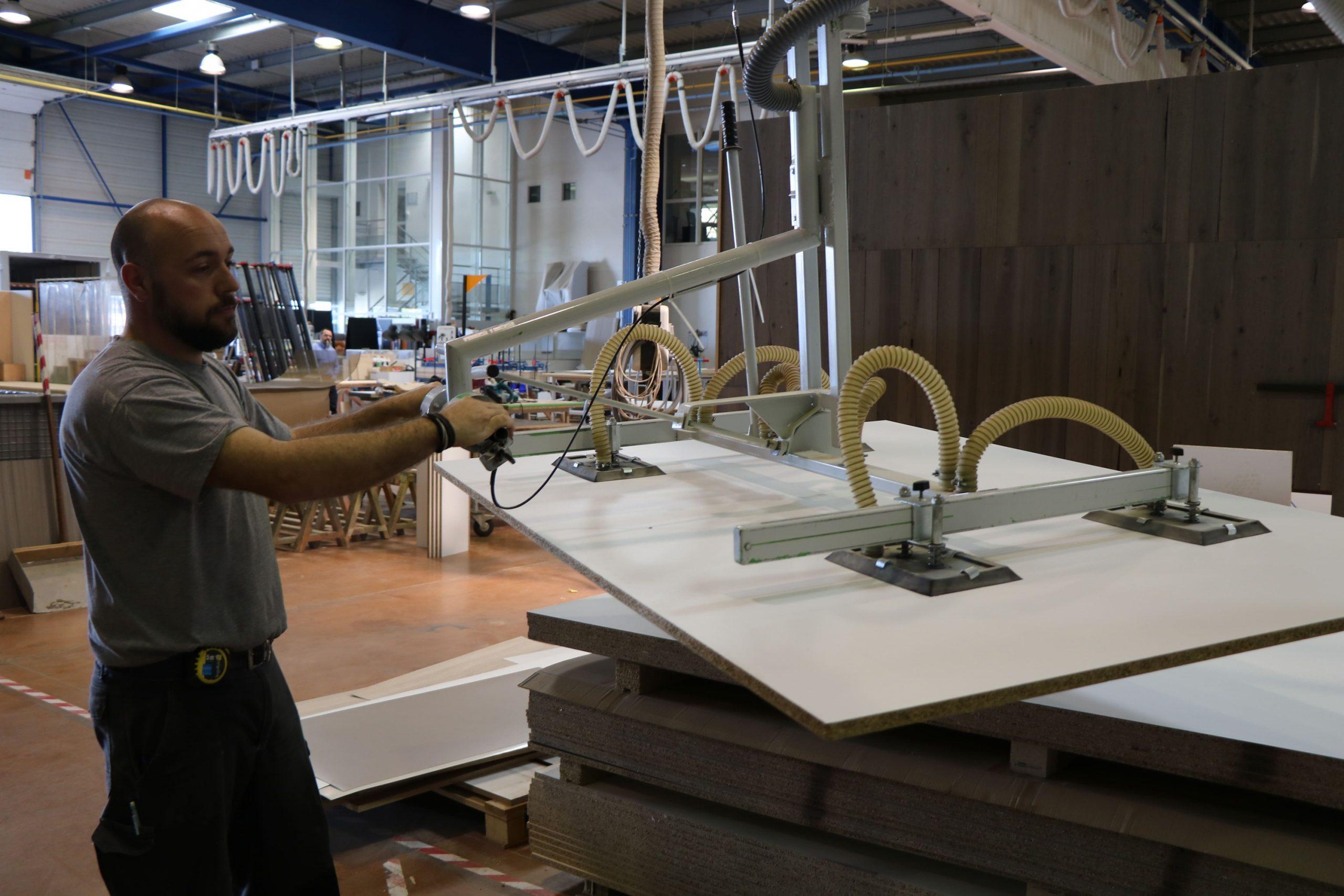 Menuisier de SAFRA Agencement utilisant une machine pour travailler les panneaux de mélaminé
